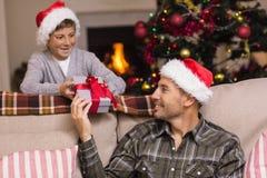 给他的儿子圣诞节礼物的父亲 免版税库存照片