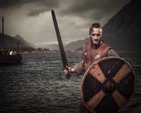 攻击的北欧海盗战士,站立沿与Drakkar的岸和山对背景 免版税库存图片