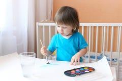 2年的可爱的小男孩年龄与刷子和油漆的在家 图库摄影