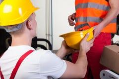 给他的同事安全帽的男性工作者 库存照片