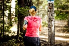 的后面女孩跑在森林的观点 库存图片