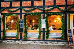 的咖啡店外部窗口和门面在圣诞节季节期间,人们休息并且交往 库存照片
