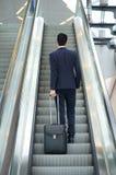 去的商人与袋子的自动扶梯 免版税库存照片