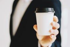 的商人拿着白皮书咖啡杯的特写镜头观点拿走 嘲笑纸盒咖啡,杯子为去外面 免版税库存图片