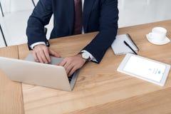 的商人研究膝上型计算机的部份观点在有片剂的工作场所 免版税库存图片