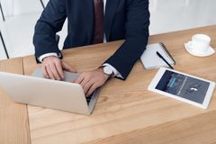 的商人研究膝上型计算机的部份观点在有片剂的工作场所 免版税库存照片