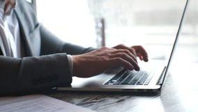 的商人运作在现代膝上型计算机的晴朗的办公室的特写镜头观点 键入在笔记本键盘的男性手 股票录像