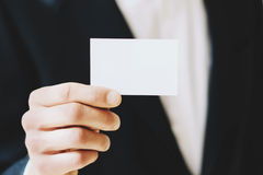 的商人给一张空的白色名片的特写镜头观点 水平的大模型,被弄脏的背景 免版税库存图片