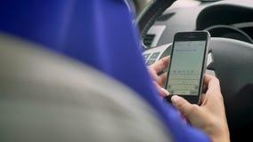 的回教妇女键入在无人驾驶一台自治的自动驾驶仪的自驾驶的方向盘的后电话的后面观点 股票视频