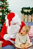 的圣诞老人和准备好逗人喜爱的女孩圣诞节 免版税库存照片