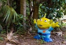 傻的外星人在热带密林庭院里 免版税库存照片
