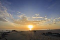 的多云天空海和海滩风景让某些人做他们的爱好在假日早晨 免版税库存图片