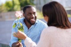 给他的夫人一朵俏丽的花的创造性的有礼貌的人 免版税库存照片
