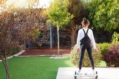 的女孩乘坐一辆电滑行车的后面观点室外 在Hoverboard的年轻少年平衡 免版税库存照片