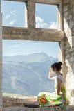 的女孩包括她的从太阳的眼睛和朝前看从窗口基石的后面观点 免版税库存照片