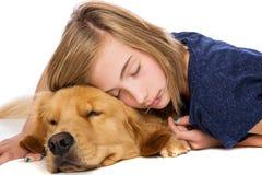 的女孩和睡着她的狗的声音 库存照片