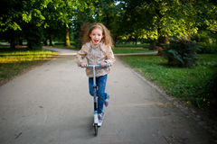 7-8年的女孩在城市公园乘坐一辆滑行车 免版税库存图片