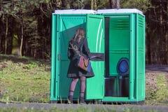 的女孩在室外的便携式的洗手间 免版税库存照片