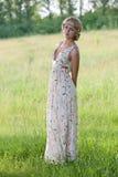 的女孩在自然的一件长的礼服 免版税库存图片