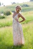 的女孩在自然的一件长的礼服 免版税库存照片