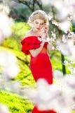 的女孩或白色性感的妇女对负,开花在嘴和头发开花有赤裸肩膀的在春天庭院里晴朗的 图库摄影
