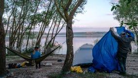 的女孩放松在享受看法的两棵树之间的橄榄色的吊床的后面观点在湖在夏天晚上一个人设定了帐篷 库存照片