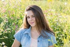 16年的女孩画象在花草甸 图库摄影