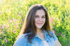 16年的女孩画象在花草甸 免版税库存照片