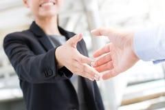 去年轻的女实业家做与商人的握手 免版税图库摄影