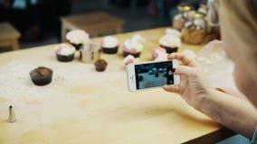 的女性为与她的特写镜头观点杯形蛋糕照相烘烤了 使用在智能手机的少妇照相机 影视素材