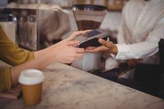 的女性顾客支付通过转账卡的大角度观点在柜台 免版税库存照片