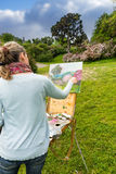 的女性画家完成她的图片的后面观点在庭院里 免版税图库摄影