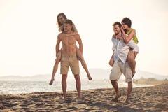 给他们的女朋友的两个年轻人扛在肩上乘驾在海滩 图库摄影