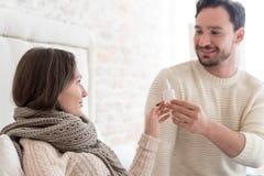 给他的女朋友滴鼻剂的可爱的快乐的人 库存图片