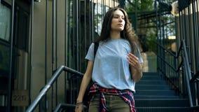 的妇女卡其色的沿着走台阶的牛仔裤和T恤杉户外 股票录像
