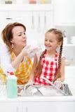 的妇女和获得的小女孩洗盘子的乐趣 免版税库存图片