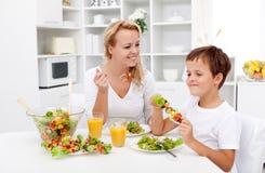 的妇女和食用的小男孩一顿健康快餐 免版税库存照片