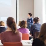 给介绍的妇女在教室里在大学 免版税库存照片