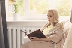 读的妇女基于长沙发和书 免版税库存照片