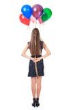 的妇女拿着在她后的后面观点气球  图库摄影