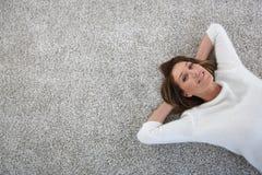 的妇女放松在地毯地板上的上部观点 免版税库存图片