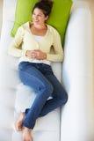 的妇女放松在沙发观看的电视上的顶上的观点 库存图片