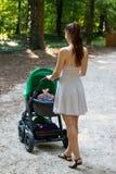 的妇女母亲拿着她的有婴孩的后面观点摇篮车在公园,少妇佩带礼服和走与摇篮车 免版税库存照片