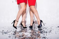 的妇女的腿特写镜头有站立在与五彩纸屑的地板上和在白色背景的党 库存图片