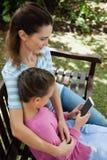 的妇女看女儿的大角度观点使用手机,当坐长凳时 免版税库存图片