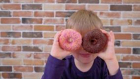 的孩子对负在两只眼睛的油炸圈饼喜欢玻璃和有乐趣 股票视频