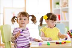 画的孩子kindergaten 孩子在托儿所绘 有笔的学龄前儿童在家 创造性的小孩 库存图片
