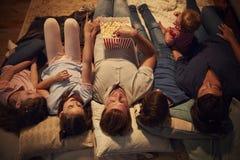 的家庭在家享受电影之夜的顶上的观点一起 图库摄影