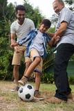 的家庭踢足球的低角度观点在围场 免版税库存图片
