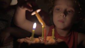 的小女孩点燃在生日蛋糕的慢动作观点蜡烛在黑暗 影视素材